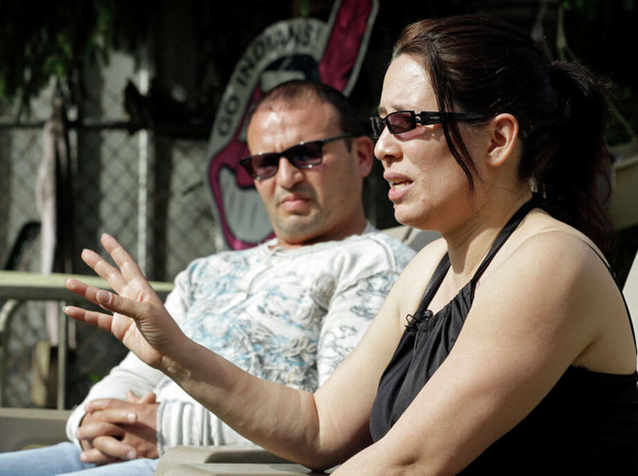 Elida Caraballo, right, talks about the abuse her late sister, Grimilda Figueroa, suffered at the hands of her common law husband, Ariel Castro, during an interview with her husband, Frank, at their home in Cleveland Thursday, May 9, 2013. Castro has been charged with kidnapping and rape for holding three women captive for a decade in his Cleveland home. (AP Photo/Mark Duncan) / AP