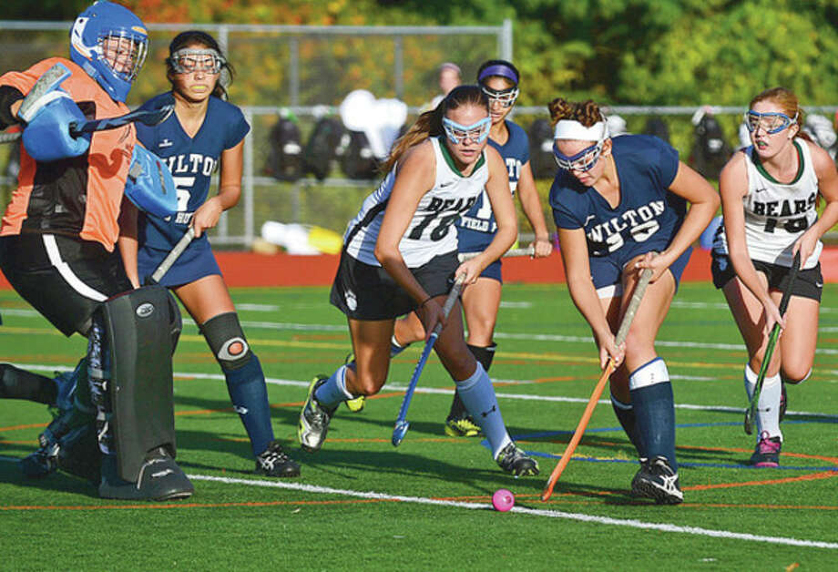Hour photo/Erik TrautmannNorwal's Emma Chassagnoux, center, defends against Wilton's Madison Hendry during Saturday's field hockey game at Testa Field. Hendry had the first goal in Wilton's 4-0 triumph.