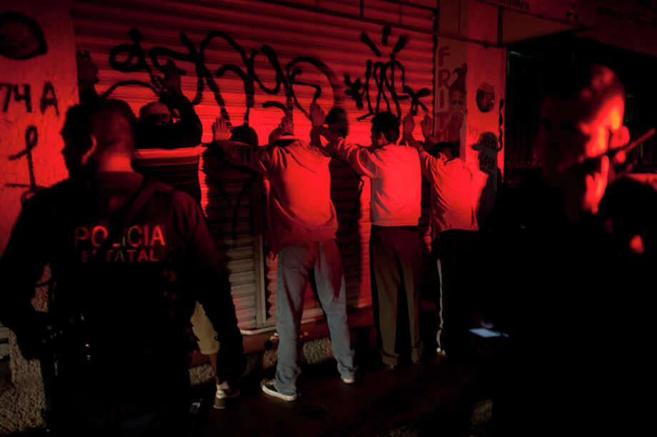 In this Sept. 18, 2012 photo, men stand with their hands on the wall after state police stopped to search them during a routine patrol in Morelia, Mexico. In cities and towns across Mexico, a nearly six-year offensive against drug cartels has been accompanied by a surge in common crime: assaults and robberies that grab no headlines but make life miserable for ordinary citizens. (AP Photo/Alexandre Meneghini) / AP