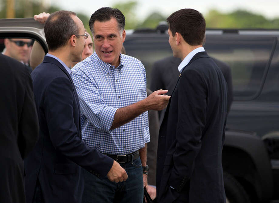 Republican presidential candidate, former Massachusetts Gov. Mitt Romney, center, talks with foreign policy adviser Dan Senor, left, and his vice presidential running mate, Rep. Paul Ryan, R-Wis., before boarding his campaign plane at Daytona International Airport, Saturday, Oct. 20, 2012, in Daytona Beach, Fla. (AP Photo/ Evan Vucci) / AP