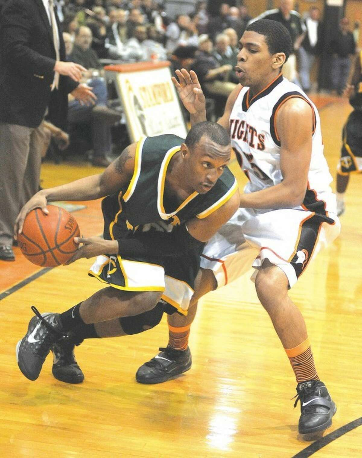 Hour file photo/John Nash - Former Stamford High basketball player Terrance Ditimi, right, seen here guarding a Trinity Catholic player, has made the roster of the University of Connecticut men's basketball team as a walk-on.