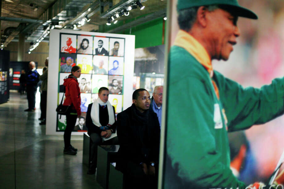 Tourists visit a temporary exhibit on Nelson Mandela at the Apartheid Museum in Johannesburg Tuesday June 11, 2013. Former South African President Nelson Mandela is spending a fourth day in a hospital, where he is being treated for a recurring lung infection. (AP Photo/Jerome Delay) / AP