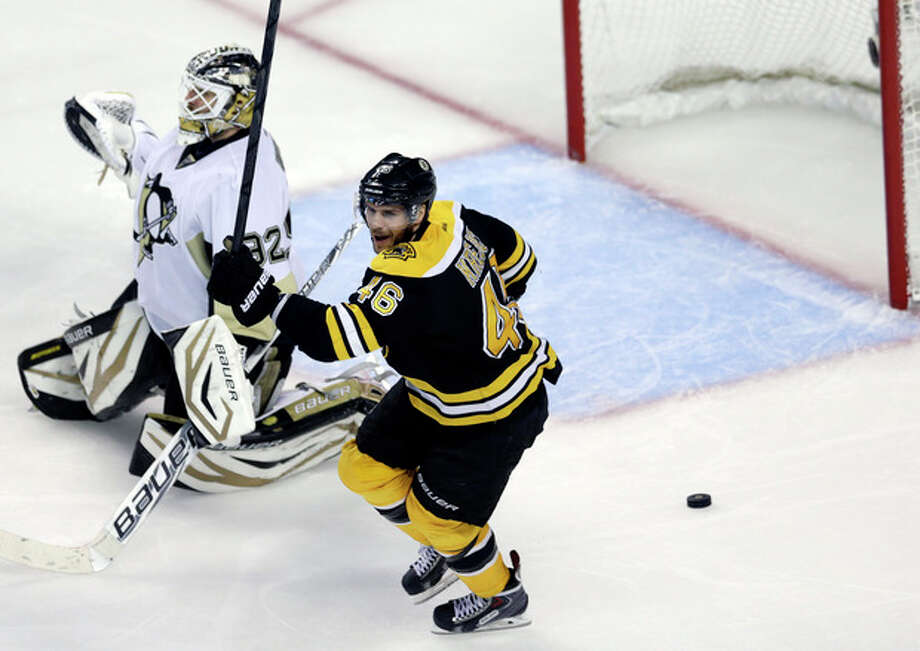 Boston Bruins center David Krejci (46) celebrates next to Pittsburgh Penguins goalie Tomas Vokoun, left, as the puck shot by Boston Bruins defenseman Adam McQuaid rattles out of the net after a goal during the third period of Game 4 in the Eastern Conference finals of the NHL hockey Stanley Cup playoffs, in Boston on Friday, June 7, 2013. (AP Photo/Charles Krupa) / AP