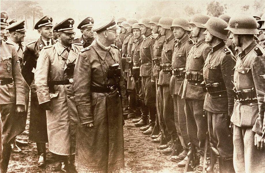 The June 3, 1944 photo provided by the US Holocaust Memorial Museum shows Heinrich Himmler, centre, SS Reichsfuehrer-SS, head of the Gestapo and the Waffen-SS, and Minister of the Interior of Nazi Germany from 1943 to 1945, as he reviews troops of the Galician SS-Volunteer Infantry Division Michael Karkoc a top commander whose Nazi SS-led unit is blamed for burning villages filled with women and children lied to American immigration officials to get into the United States and has been living in Minnesota since shortly after World War II, according to evidence uncovered by The Associated Press. Michael Karkoc became a member of the Galician division after the Ukrainian Self Defense Legion was incorporated into it near the end of the war. (AP photo/ U.S. Holocaust Memorial Museum, courtesy of Atlantic Foto Verlag Berlin) / U.S. Holocaust Memorial Museum, courtesy of Atlantic Foto Verlag