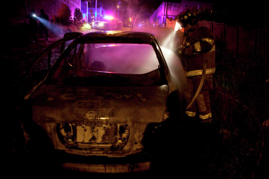 In this Sept. 18, 2012 photo, a firefighter puts out a smoldering car allegedly used in a robbery at a Coca-Cola distribution center in Morelia, Mexico. The robbers pistol-whipped three security guards, grabbed thousands of pesos in cash and fled. In cities and towns across Mexico, a nearly six-year offensive against drug cartels has been accompanied by a surge in common crime: assaults and robberies that grab no headlines but make life miserable for ordinary citizens. (AP Photo/Alexandre Meneghini) / AP