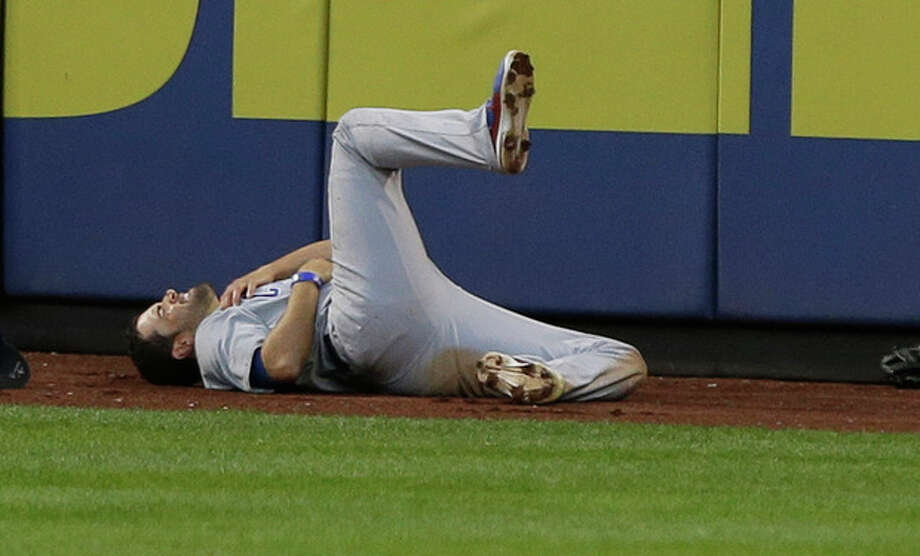 Chicago Cubs center fielder David DeJesus reacts after running to the wall during the third inning of a baseball game against the New York Mets, Friday, June 14, 2013, in New York. DeJesus was hurt on the play. (AP Photo/Frank Franklin II) / AP