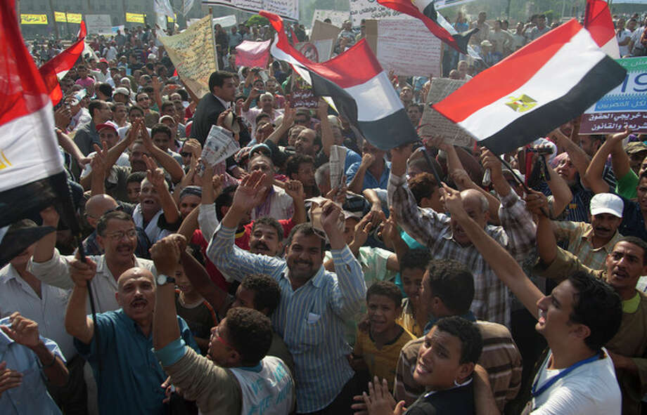 Protesters chant anti-government slogans during a rally in Tahrir Square in Cairo, Egypt, Friday, Oct. 19, 2012. Several thousand Egyptian protesters are rallying in Cairo to demand the president and his Muslim Brotherhood supporters ensure the country's constitution represents all factions of society. (AP Photo/Khalil Hamra) / AP