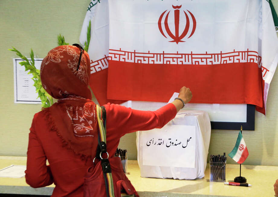 A woman places her ballot in a box as Iranians outside their country of origin cast ballots in Iran's presidential election, in a hotel meeting room in Los Angeles Friday, June 14, 2013. Iranian-Americans and expatriates cast ballots Friday in polling places across the United States, joining their countrymen half a world away in selecting the next Iranian president (AP Photo/Reed Saxon) / AP