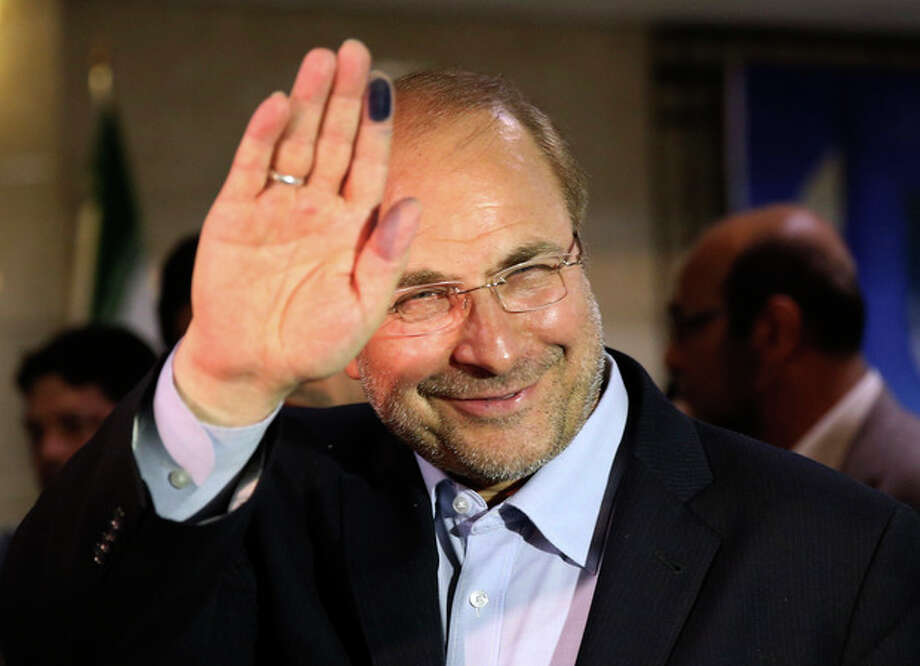 FILE -- Tehran's mayor, Mohammad Bagher Qalibaf, a former Revolutionary Guard commander, waves to media with an ink-stained finger, after registering his candidacy for the upcoming presidential election, at the election headquarters of the interior ministry in Tehran, Iran, Saturday May 11, 2013. Iran's reformist-backed presidential candidate Hasan Rowhani surged to a wide lead in early vote counting, the Interior Ministry reported, well ahead of Tehran Mayor Mohammad Bagher Qalibaf, who was running second.Qalibaf was boosted by a reputation as a steady hand for Iran's sanctions-wracked economy. (AP Photo/Ebrahim Noroozi, File) / AP