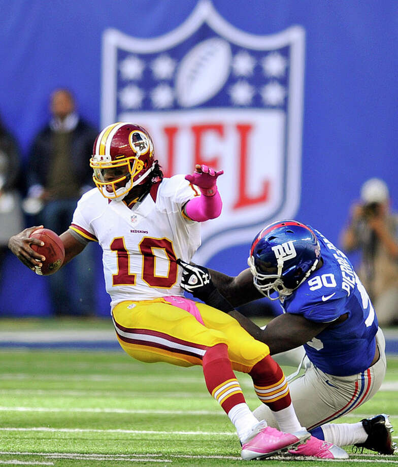 Washington Redskins quarterback Robert Griffin III (10) is sacked by New York Giants defensive end Jason Pierre-Paul (90) during the second half of an NFL football game, Sunday, Oct. 21, 2012, in East Rutherford, N.J. (AP Photo/Bill Kostroun) / FR59151 AP
