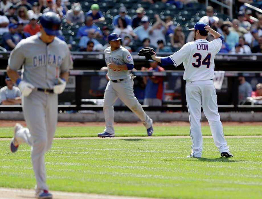 New York Mets relief pitcher Brandon Lyon (34) waits for the ball after walking Chicago Cubs' Cody Ransom (1) with bases loaded as Welington Castillo (53) heads to home plate for a run during the eighth inning of a baseball game Saturday, June 15, 2013, in New York. (AP Photo/Frank Franklin II) / AP