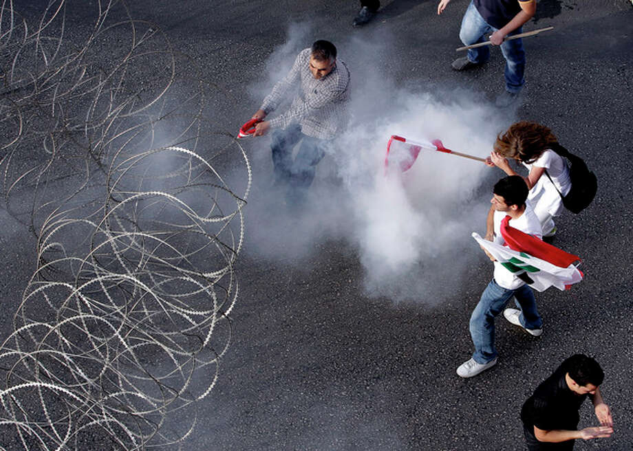 Lebanese protesters are enveloped in tear gas as they pull a barbed-wire barrier during clashes after the funeral of Brig. Gen. Wissam al-Hassan who was assassinated on Friday by a car bomb in Beirut, Lebanon, Sunday Oct. 21, 2012. Lebanese soldiers fired guns and tear gas to push back hundreds of protesters who broke through a police cordon and tried to storm the government headquarters in Beirut. The enraged crowd came from the funeral of a top Lebanese intelligence official assassinated in a massive car bombing.(AP Photo/Hussein Malla) / AP