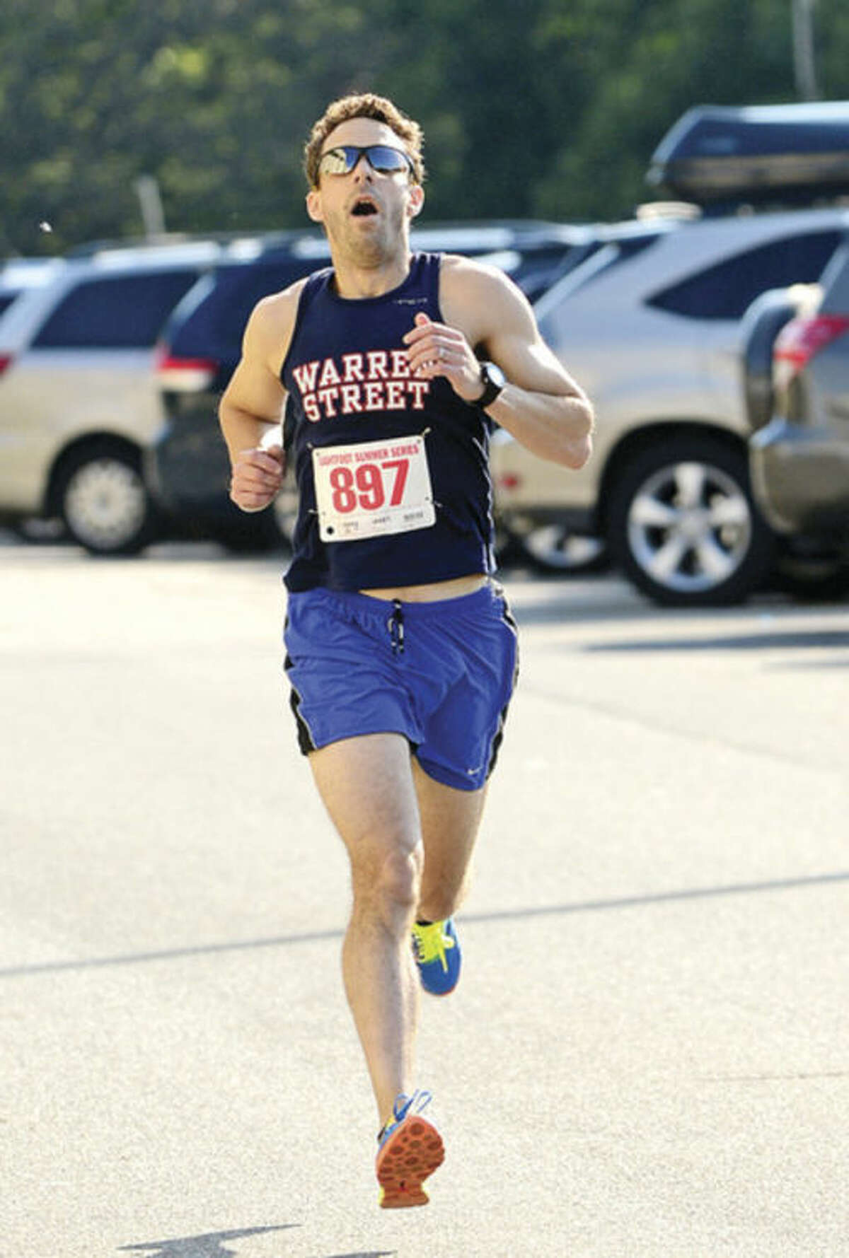 New Cannan Resident Larry Ikard finishes first for the men during Lightfoot's opening race of the Norwalk Running Series, a 3-mile race which begins and ends at Norwalk High School. Hour photo / Erik Trautmann