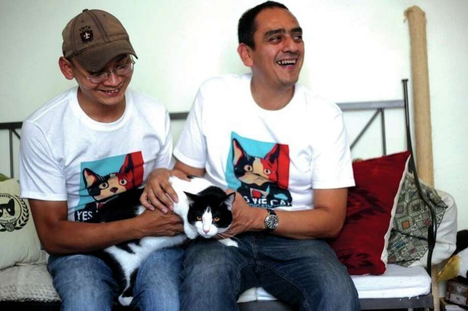 AP photo / Felix MarquezDiego Cruz, left, and Sergio Chamorro pose with their cat Morris in their home in Xalapa, Mexico, Saturday. He is attracting tens of thousands of politician-weary, two-legged supporters on social media. / AP