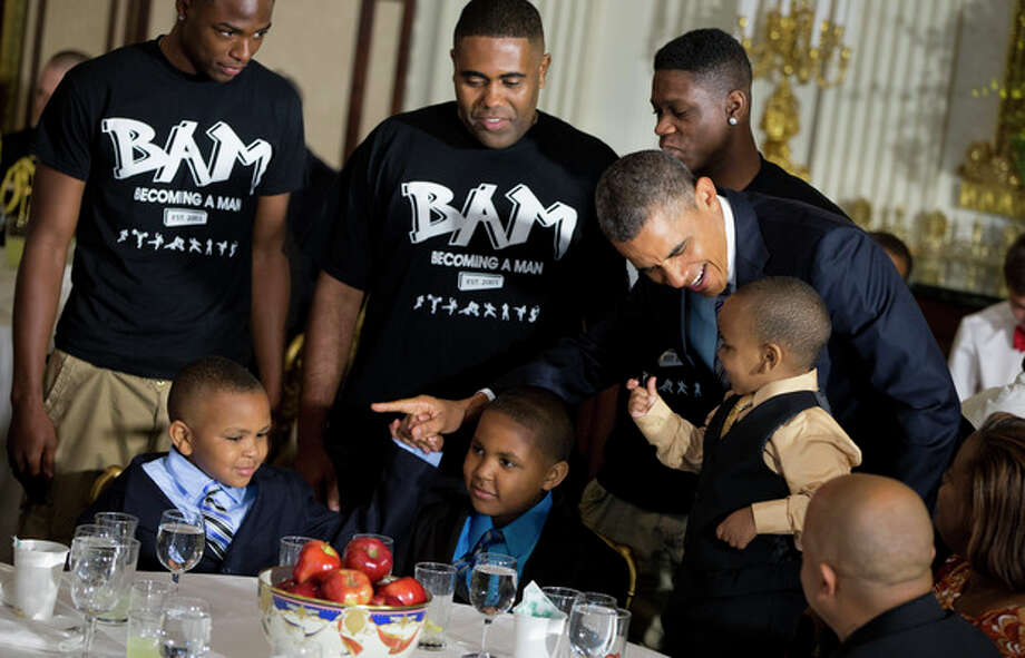 President Barack Obama greets guests, including fathers and their children participants in the Becoming a Man (BAM) program at Hyde Park Academy in Chicago, Friday, June 14, 2013, in the State Dining Room of the White House in Washington, where the president hosted a Father's Day luncheon. (AP Photo/Evan Vucci) / AP