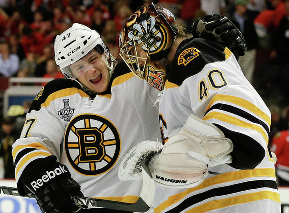 Boston Bruins defenseman Torey Krug (47) celebrates with goalie Tuukka Rask (40) after the Bruins scored a goal against the Chicago Blackhawks in sudden death overtime during Game 2 of the NHL hockey Stanley Cup Finals, Saturday, June 15, 2013, in Chicago. The Bruins won 2-1. (AP Photo/Nam Y. Huh) / AP