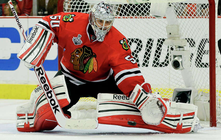 Chicago Blackhawks goalie Corey Crawford (50) gloves the puck on a shot attempt by the Boston Bruins during Game 2 of the NHL hockey Stanley Cup Finals, Saturday, June 15, 2013, in Chicago. (AP Photo/Nam Y. Huh) / AP