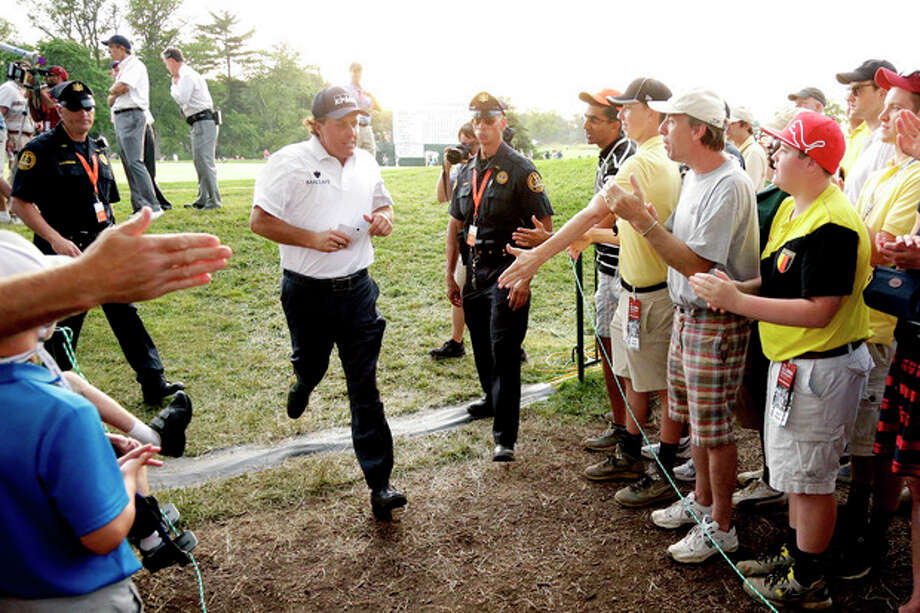 Phil Mickelson jogs off the 18th green after the third round of the U.S. Open golf tournament at Merion Golf Club, Saturday, June 15, 2013, in Ardmore, Pa. (AP Photo/Gene J. Puskar) / AP