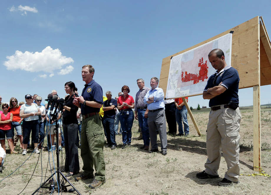 Incident commander Rich Harvey, center, talks about the progress of the Black Forest Fire in Colorado Springs, Colo., Saturday, June 15, 2013. The number of homes destroyed in Colorado's most destructive wildfire ever continues to rise. Authorities reported early Saturday that 473 houses had been incinerated. That compares with a report of a little over 400 just a few hours earlier.(AP Photo/Marcio Jose Sanchez) / AP