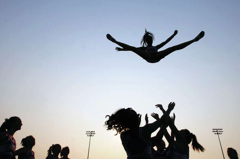 AP file photo / The Idaho Press-Tribune, Charlie LitchfieldIn this Sept. 9, 2011, file photo, a cheerleader from Nampa High School is thrown into the air as the cheer squad practices their stunts before a game in Nampa, Idaho. In a new policy statement released online Monday in the journal Pediatrics, the American Academy of Pediatrics says school sports associations should designate cheerleading as a sport, and make it subject to safety rules and better supervision. / The Idaho Press-Tribune