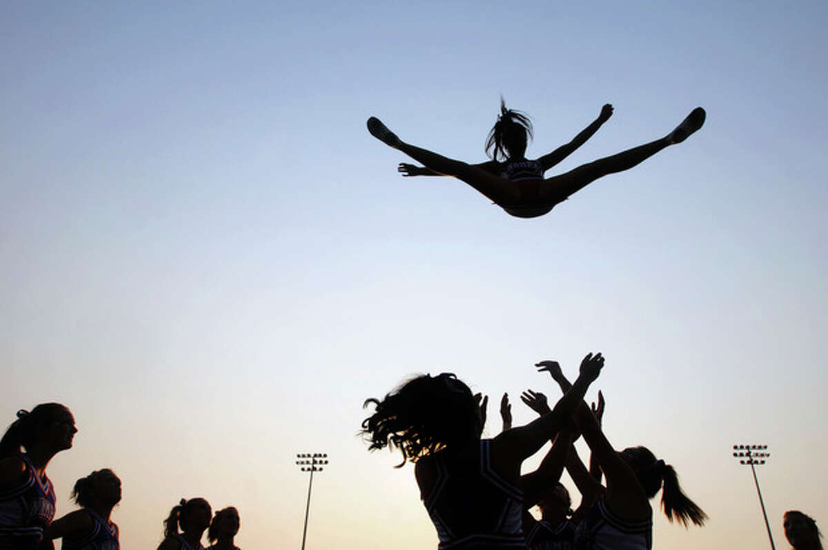 FILE - In this Sept. 9, 2011 file photo, a cheerleader from Nampa High School is thrown into the air as the cheer squad practices their stunts before a game in Nampa, Idaho. In a new policy statement released online Monday, Oct. 22, 2012 in the journal Pediatrics, the American Academy of Pediatrics says school sports associations should designate cheerleading as a sport, and make it subject to safety rules and better supervision. (AP Photo/The Idaho Press-Tribune, Charlie Litchfield, File)