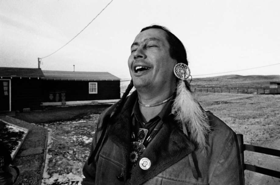 "FILE - In a Feb. 4, 1974 file photo, American Indian Movement (AIM) leader Russell Means, who is challenging incumbent Oglala Sioux Tribal President Richard Wilson in Thursday's election on the Pine Ridge Indian Reservation, laughs at news report which quoted Wilson as saying he will give AIM 10 days to get off the reservation after he is reelected ""or else"", in Pine Ridge, S.D. Means, a former American Indian Movement activist who helped lead the 1973 uprising at Wounded Knee, reveled in stirring up attention and appeared in several Hollywood films, died early Monday, Oct. 22, 2012 at his ranch in in Porcupine, S.D., Oglala Sioux Tribe spokeswoman Donna Solomon said. He was 72. (AP Photo/Jim Mone, File) / AP"