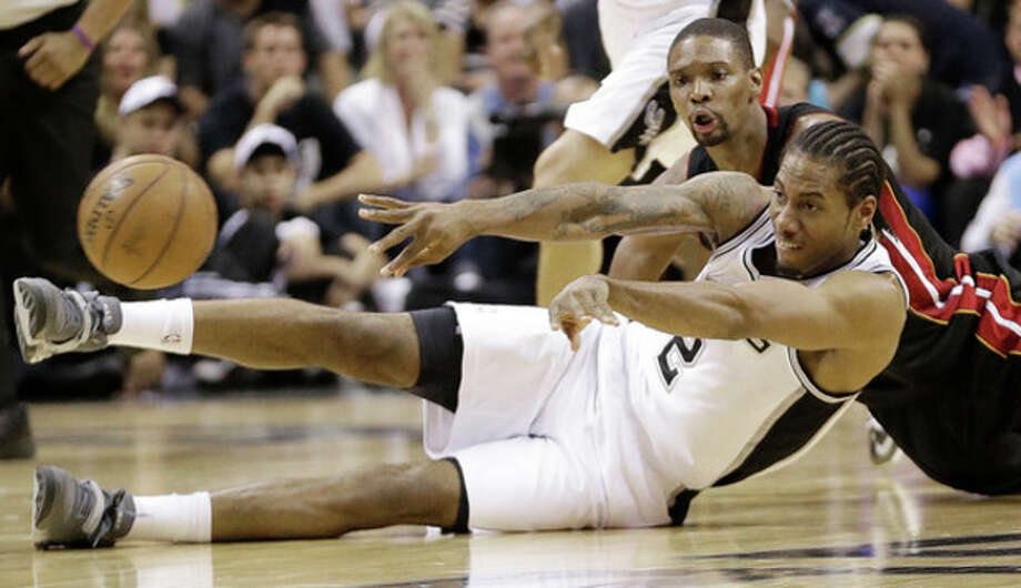 San Antonio Spurs' Kawhi Leonard (2) passes the ball as he and Miami Heat's Chris Bosh hit the floor during the first half at Game 5 of the NBA Finals basketball series, Sunday, June 16, 2013, in San Antonio. (AP Photo/Eric Gay) / AP