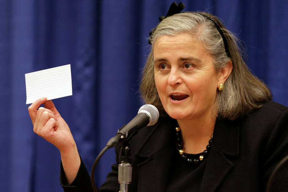 Kathryn Condon, executive director, Army National Military Cemeteries, holds up an index card demonstrating how Arlington National Cemetery used to store their records, as she presentsed the ANC Explorer application for the cemetery, Monday, Oct. 22, 2012, during a news conference in Washington. Arlington National Cemetery plans to make available to the public the detailed geospatial database it has developed over several years while overhauling its records and responding to reports of misidentified remains. The database will be available over the Internet and through a mobile phone app that visitors to the cemetery can take with them to find a specific gave anywhere in the cemetery. (AP Photo/Jacquelyn Martin) / AP