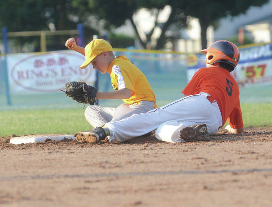 Hour photo/Matthew VinciJimmy Evans of the Laurel Athletic Club, right, is out at second base after being tagged by Korey Morton of the Lions Club during Monday night's Norwlk Little League Majors Division championship game. The Lions claimed the title with a 10-0 victory.