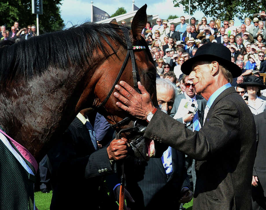 FILE - This is a Aug 22, 2012 file photo of race horse trainer Henry Cecil as he greets Frankel after his victory in the Juddmonte International Stakes during day one of the 2012 Ebor Festival at York Racecourse York England. Cecil, one of British horse racing's most successful trainers with 25 British Classic winners, has died. it was announced Tuesday June 11, 2013. He was 70. Cecil's greatest horse in his 44 years as trainer was Frankel, who retired last year after winning all 14 of his races. (AP Photo/ John Giles/PA. File) / PA