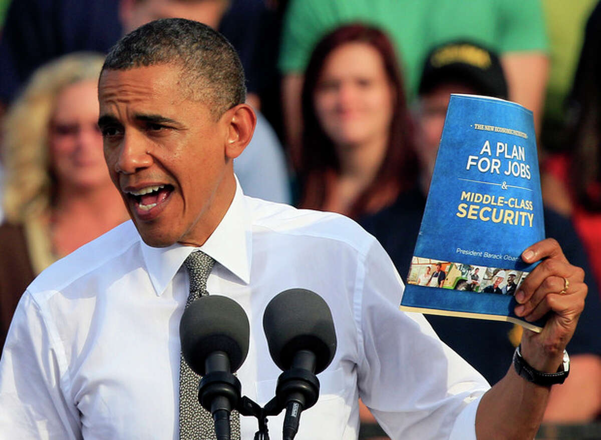 President Barack Obama holds up a copy of job plan during a joint campaign appearance with Vice President Joe Biden, not seen, Tuesday, Oct. 23, 2012, at Triangle Park in Dayton, Ohio. (AP Photo/Al Behrman)