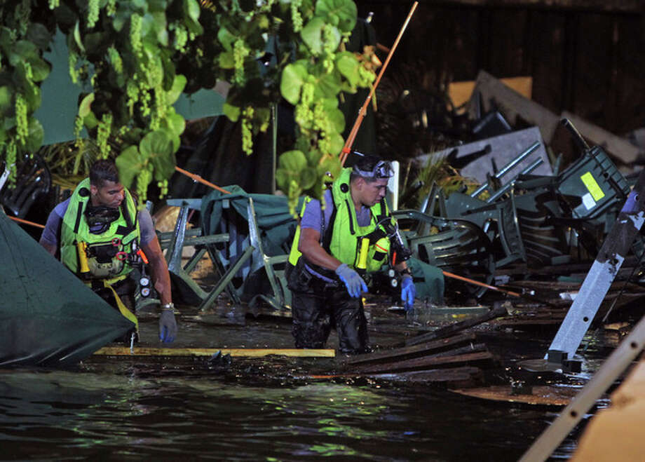 Rescue divers search for missing persons after a packed outdoor deck collapsed at popular Miami-area sports bar Thursday June 13, 2013. Lt. Ignatius Carroll of Miami Fire-Rescue said late Thursday that 100 people fell into the water. He said rescuers pulled patrons from the bay, and that divers were searching waters underneath the collapsed deck as helicopters shined spotlights onto the area. (AP Photo/Miami Herald, Walter Michot) / Miami Herald