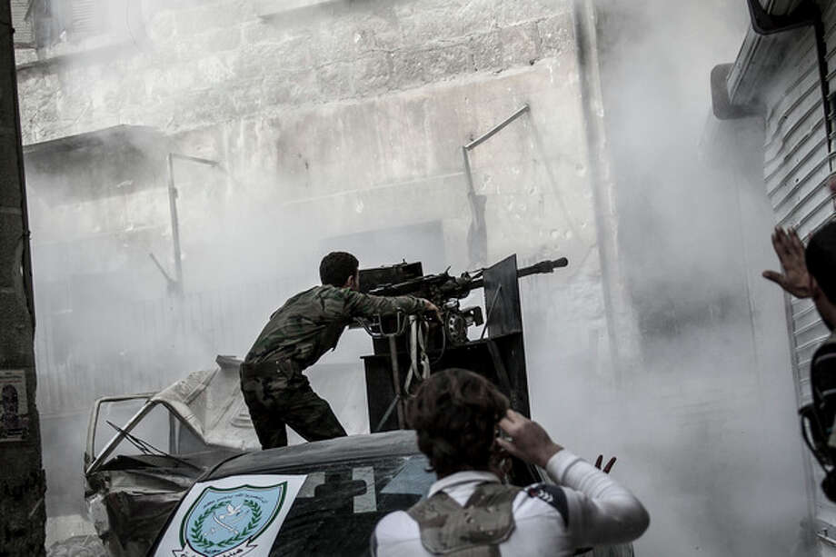 In this Wednesday, Oct. 24, 2012 photo, a Free Syrian Army fighter shoots a gun as rebel fighters belonging to the Liwa Al Tawhid group carry out a military operation at the Karmal Jabl front line, in Aleppo, Syria. (AP Photo/Narciso Contreras). / Narciso Contreras
