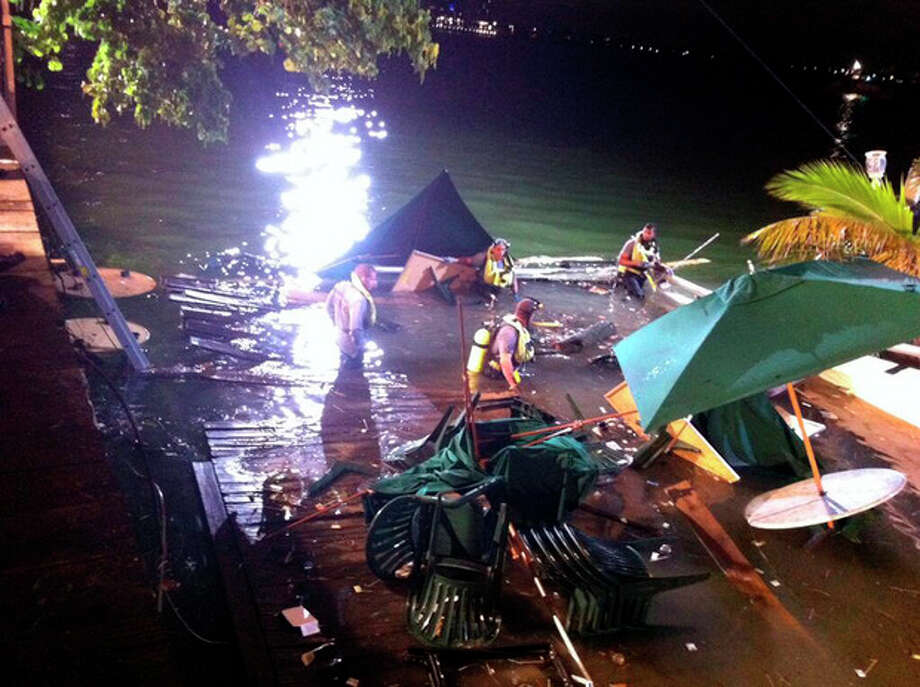 In this photo provided by WSVN-TV, divers search the water after a deck collapse at Shuckers Bar & Grill in Miami Thursday night, June 13, 2013. The deck collapsed during the NBA Finals on Thursday night, sending dozens of patrons into the shallow waters of Biscayne Bay. Three people were critically injured. (AP Photo/WSVN-TV, Tom Tuckwell) MANDATORY CREDIT / WSVN-TV