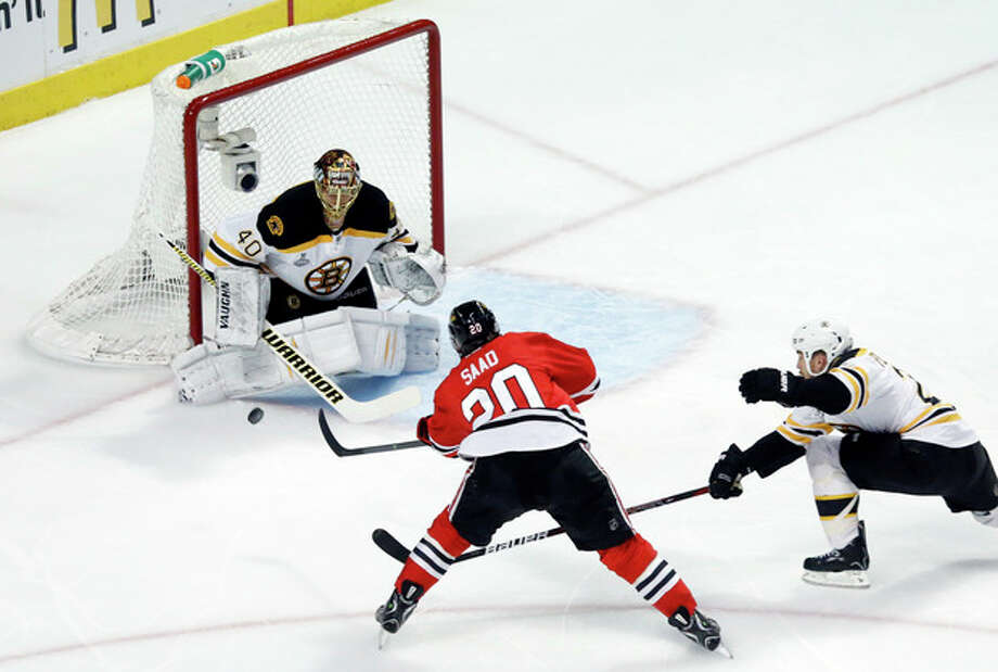 Boston Bruins goalie Tuukka Rask (40) saves a shot by Chicago Blackhawks left wing Brandon Saad (20) during the first period of Game 1 in their NHL Stanley Cup Final hockey series,Wednesday, June 12, 2013 in Chicago. (AP Photo/Charles Rex Arbogast) / AP