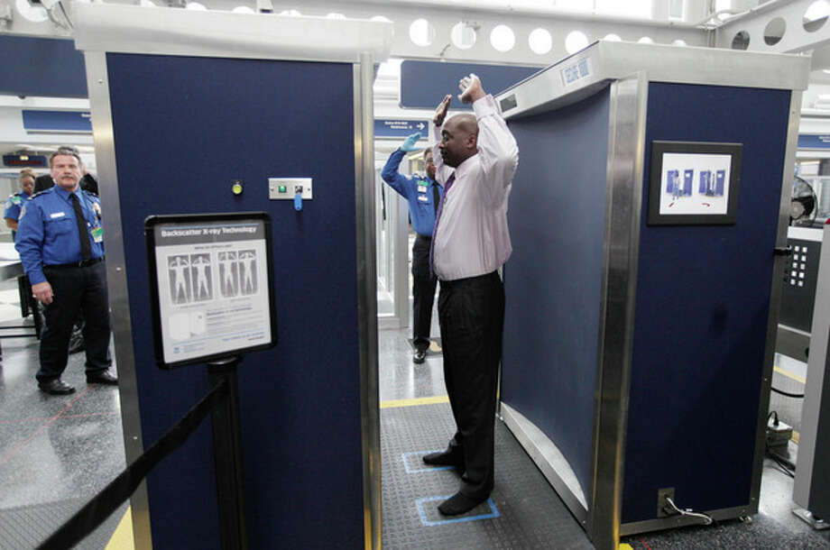 FILE - In this March 15, 2010 file photo, a volunteer passes through the first full body scanner installed at O'Hare International Airport in Chicago. The Transportation Security Administration has been replacing the huge X-ray machines with smaller, millimeter wave body scanners at seven major U.S. airports. The new technology produces a cartoon-like outline rather than naked images of passengers produced by using X-rays. (AP Photo/M. Spencer Green, File) / AP