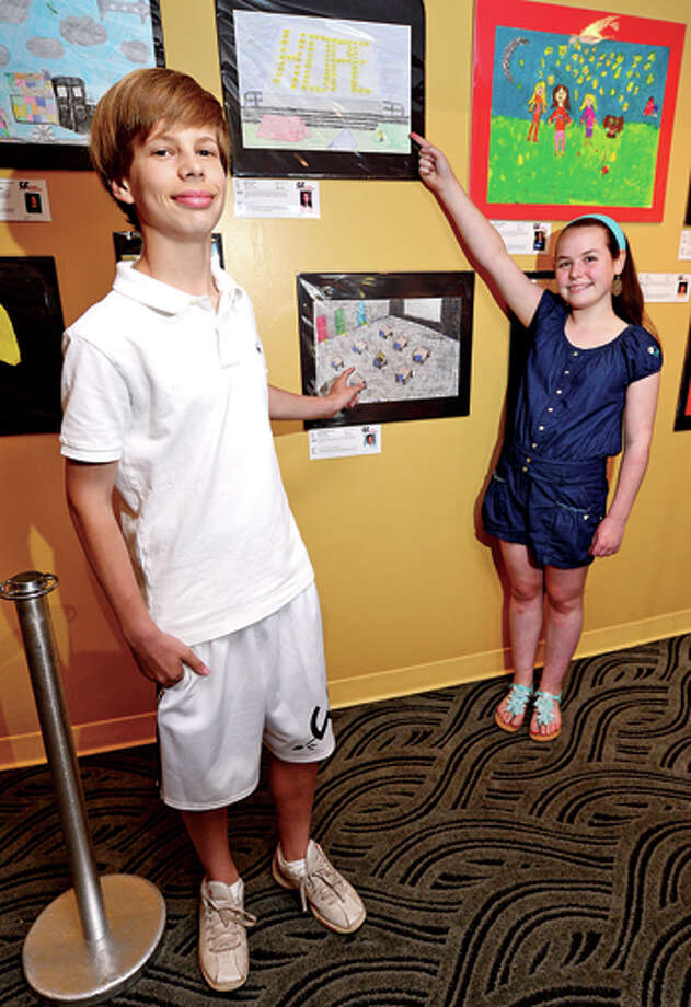 "Middlebrook Seventh graders, Michael Hueglin and Molly Thomas, had their art work selected to be in the 2013 International Children's Art Exhibit, ""Bringing My Culture to Light: Illuminate!"" at the Maritime Aquarium at Norwalk.Molly's piece, ""Sparks of Hope, ""and Michael's piece, ""Knowledge Opens Doors,"" were two of 150 pieces of work selected from 20 countries of over 1,000 submissions and as part of Wilton Public Schools' Fine and Performing Arts' annual International Art Exchange program. Their works will be sent to partner countries in Cambodia and Ireland.  / (C)2013, The Hour Newspapers, all rights reserved"