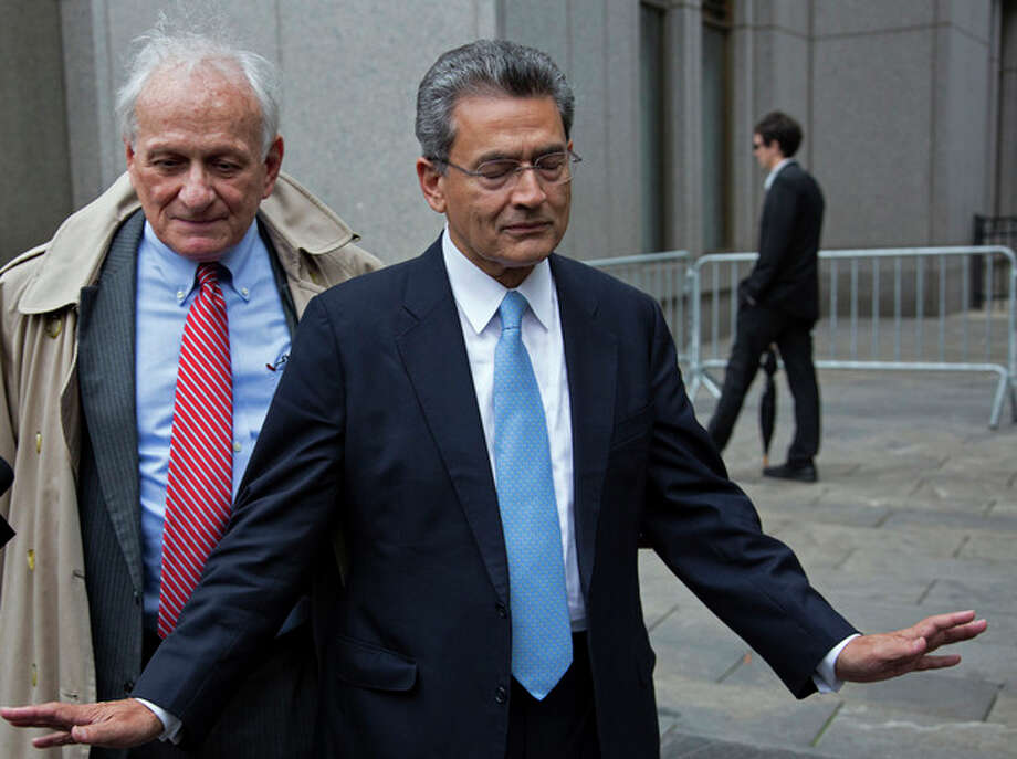 Rajat Gupta, right, declines to answer questions as he leaves federal court in New York, Wednesday, Oct. 24, 2012 after the former Goldman Sachs and Procter & Gamble Co. board member was sentenced Wednesday to 2 years in prison for feeding inside information about board dealings with a billionaire hedge fund owner who was his friend. Left is Gupta's attorney Gary Naftalis. (AP Photo/Craig Ruttle) / FR61802 AP