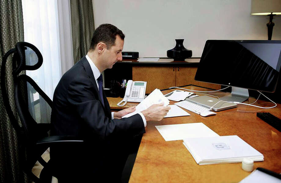 This photo released on the official Facebook page of Syrian President Bashar Assad, shows Syrian president Bashar Assad working in his office, in Damascus, Syria, Thursday, June 13, 2013. State TV quoted Transpiration Minister as saying that a mortar round fell on the edge of the airport delaying two flights that were going to land one from Latakia and one from Kuwait. The attack also delayed the take off of a Syrian flight to Baghdad. None of the planes or there passengers were hit. (AP Photo) / THE OFFICIAL FACEBOOK PAGE OF SYRIAN PRESIDENT BASHAR ASSAD