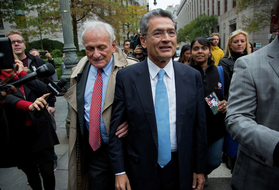Rajat Gupta, center right, leaves federal court in New York, Wednesday, Oct. 24, 2012 after the former Goldman Sachs and Procter & Gamble Co. board member was sentenced Wednesday to 2 years in prison for feeding inside information about board dealings with a billionaire hedge fund owner who was his friend. At left is Gupta's attorney, Gary Naftalis. (AP Photo/Craig Ruttle) / FR61802 AP