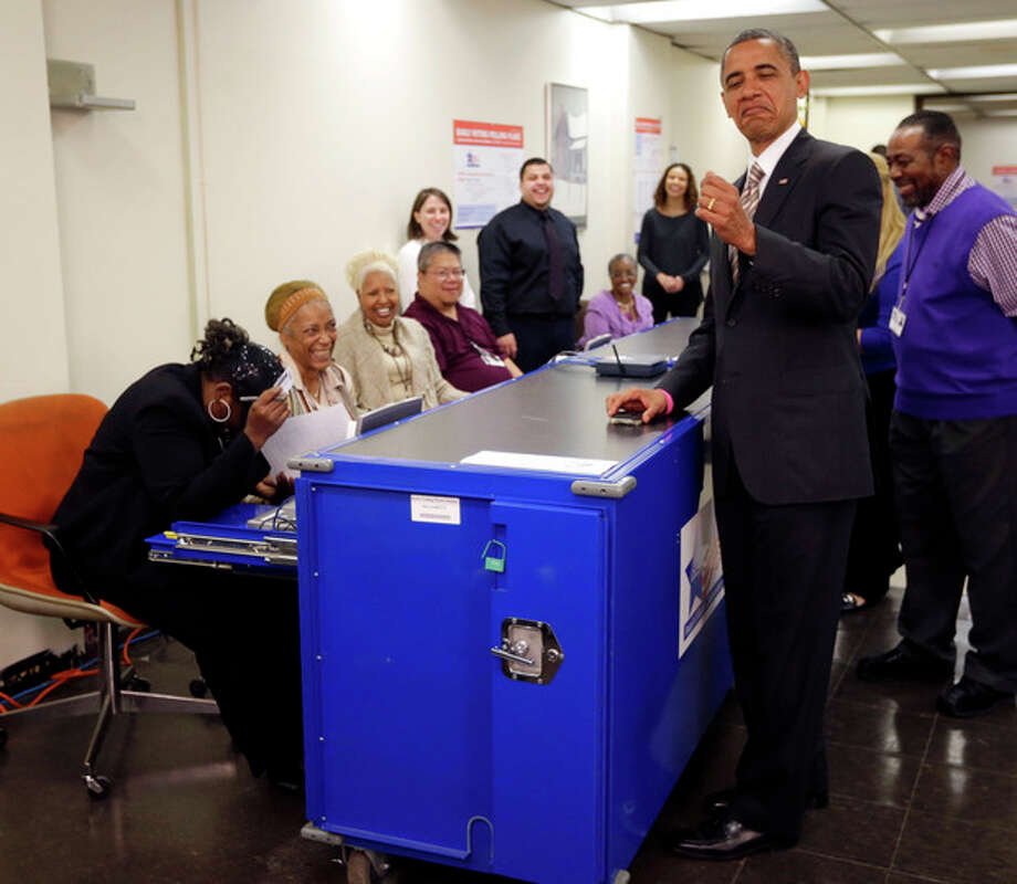President Barack Obama playfully jokes around with the way election official Marie Holmes, left, looked over his drivers license during early voting, in the 2012 election at the Martin Luther King Community Center, Thursday, Oct. 25, 2012, in Chicago. (AP Photo/Pablo Martinez Monsivais) / AP