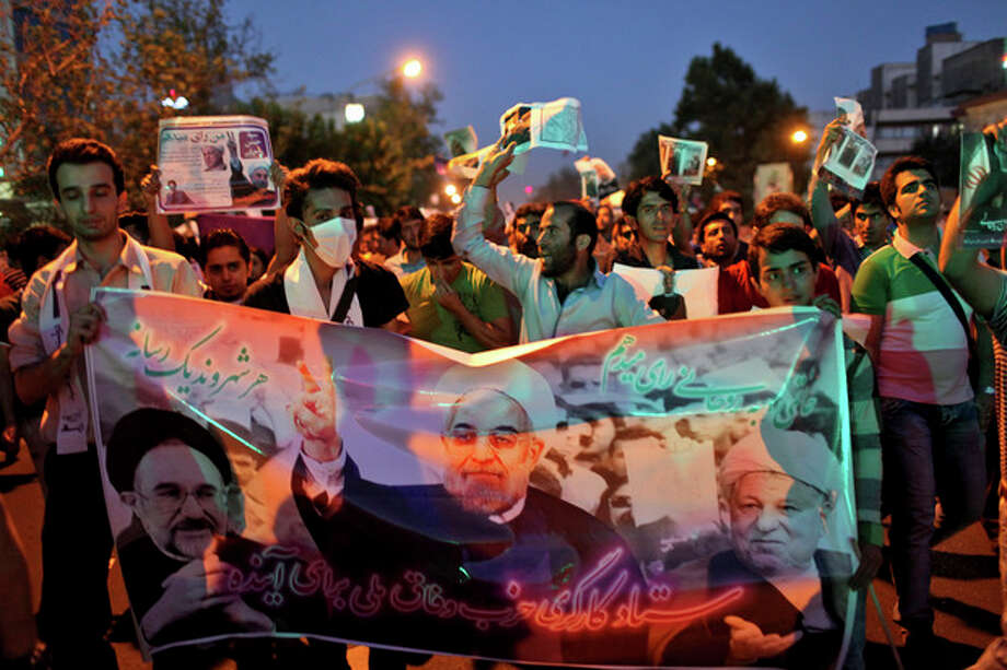 Supporters of the Iranian presidential candidate Hasan Rowhani, former Iranian nuclear negotiator, chant slogans, as they hold a banner containing pictures of Rowhani, center, former Presidents Akbar Hashemi Rafsanjani, right, and Mohammad Khatami, during a street campaign, in Tehran, Iran,Wednesday, June 12, 2013. The presidential election will be held on June 14. (AP Photo/Ebrahim Noroozi) / AP