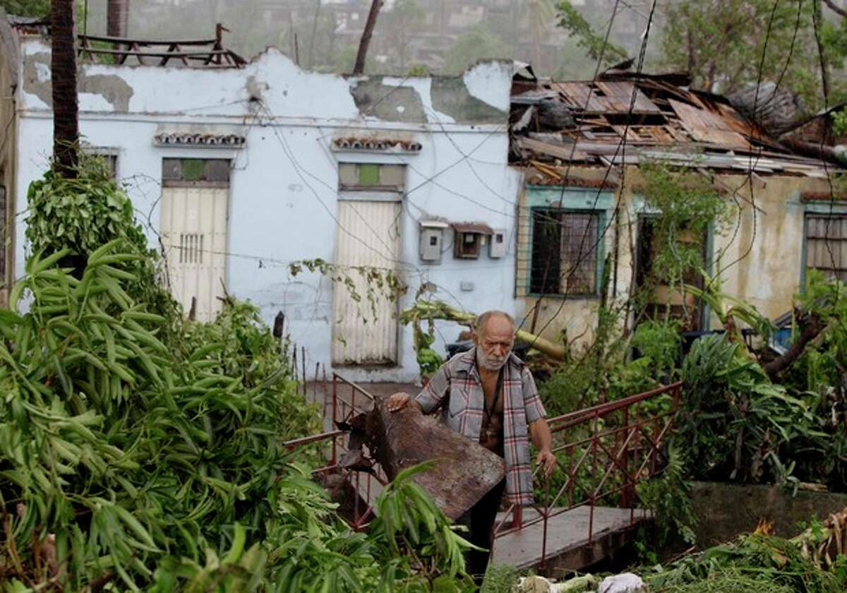 A man tries to recover his belongings from his house destroyed by Hurricane Sandy in Santiago de Cuba, Cuba, Thursday Oct. 25, 2012. Hurricane Sandy blasted across eastern Cuba on Thursday as a potent Category 2 storm and headed for the Bahamas after causing at least two deaths in the Caribbean. (AP Photo/Franklin Reyes)