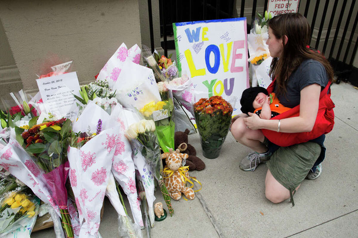 A woman looks at a memorial outside the apartment building where the two children allegedly stabbed by their nanny, Friday, Oct. 26, 2012, in New York. The 2-year-old son and 6-year-old daughter of a CNBC executive were found dead by their mother in a dry bathtub in the family's Upper West Side apartment Thursday night. The nanny suspected of stabbing the children was in critical condition Friday with apparently self-inflicted injuries. (AP Photo/John Minchillo)