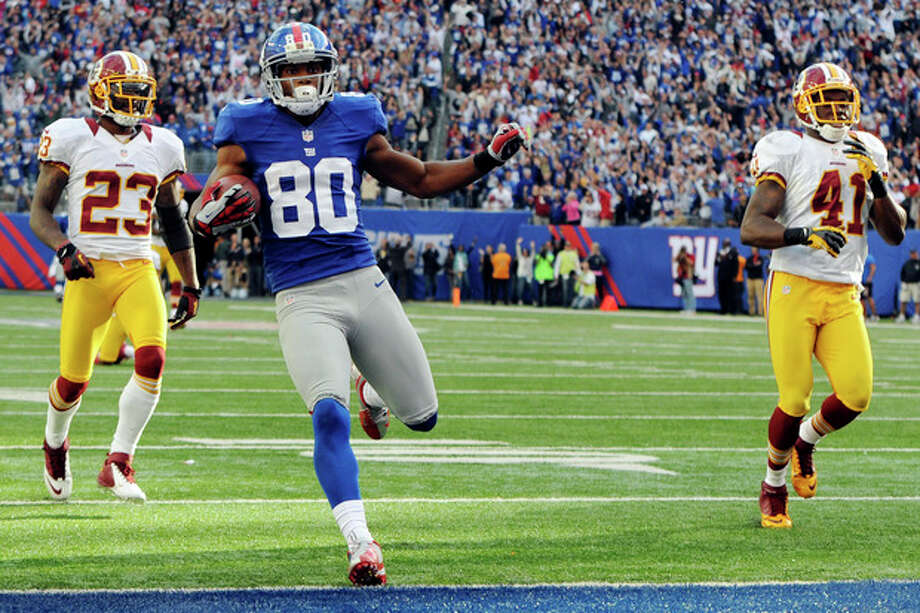 New York Giants' Victor Cruz scores the winning touchdown ahead of Washington Redskins' DeAngelo Hall (23) and Madieu Williams (41) during the fourth quarter of an NFL football game, Sunday, Oct. 21, 2012, in East Rutherford, N.J. The Giants won 27-23. (AP Photo/The Record of Bergen County, Tyson Trish) MAGS OUT; TV OUT; NO ARCHIVING; MANDATORY CREDIT / The Record of Bergen County