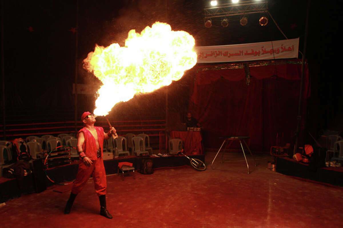 In this photo taken Thursday, Oct. 25, 2012, Rifat al-Gureisy, 55, a member of the Egyptian National Circus blows fire during a practice in Gaza City. The circus came to Gaza on Friday, accompanied by blaring music, juggling clowns and fire blowers ?- but getting it there required its own high-wire act. No women performers were included for fear of offending conservative Palestinians and the Gaza Strip's militant Hamas rulers, and the circus' lone lion and tiger were left behind because of the high cost of transporting them legally into Gaza. (AP Photo/Adel Hana)