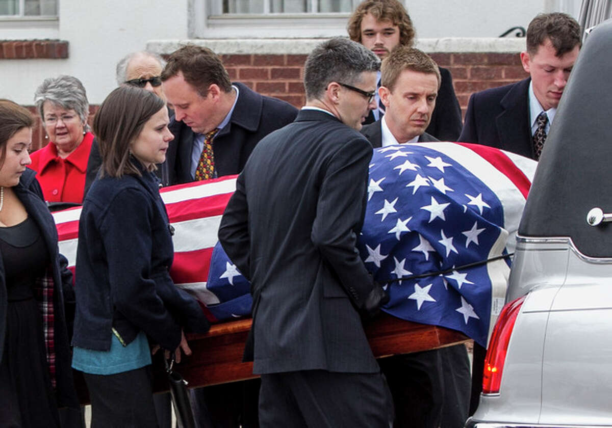 Family members place the casket of former Democratic U.S. Senator and three-time presidential candidate George McGovern onto a hearse as it is being transported to the Washington Pavilion of Arts and Science in Sioux Falls, S.D., for the funeral service, Friday, Oct. 26, 2012. McGovern died Sunday in his native South Dakota at age 90. (AP Photo/Nati Harnik)