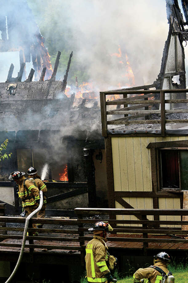 Firefighters battle a blaze that gutted a home at 202 Steep Hiull Road in Weston THursday afternoon. Hour photo / Erik Trautmann / (C)2013, The Hour Newspapers, all rights reserved