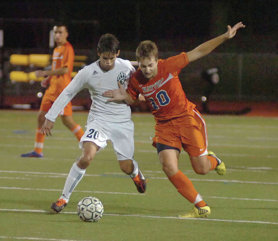 Hour photo/John NashNorwalk's Nacho Navarro, left, battles Danbury's Kenny Wilson for possession of a ball during Friday night's FCIAC quarterfinal at Testa Field in Norwalk. The top-seeded Bears scored a 2-0 victory and will face Wilton in Monday's semis.