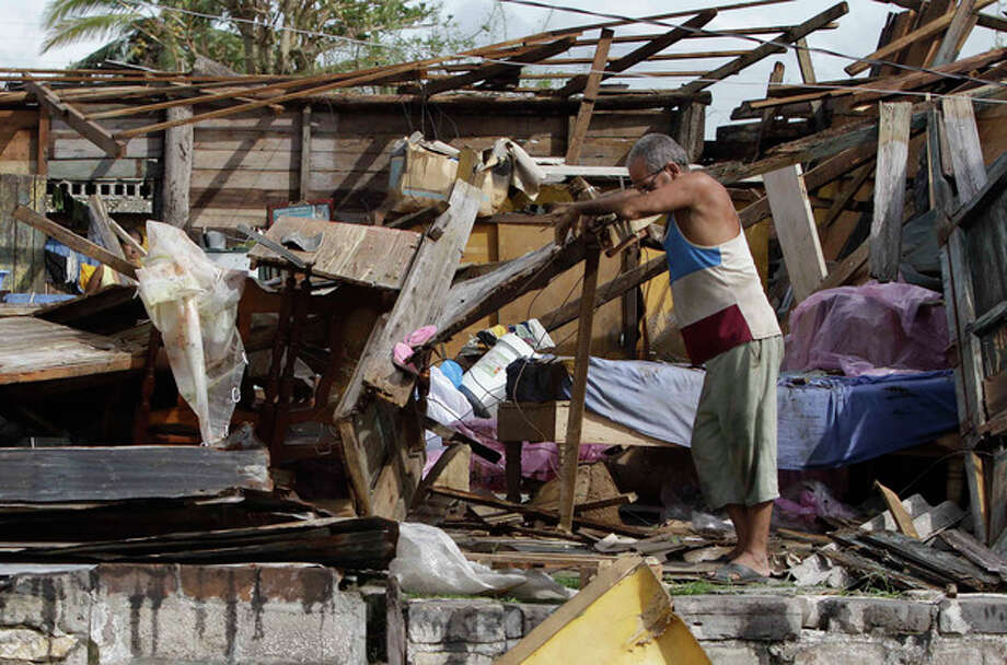 Resident Antonio Garces tries to recover his belongings from his house destroyed by Hurricane Sandy in Aguacate, Cuba, Thursday Oct. 25, 2012. Hurricane Sandy blasted across eastern Cuba on Thursday as a potent Category 2 storm and headed for the Bahamas after causing at least two deaths in the Caribbean. (AP Photo/Franklin Reyes) / AP